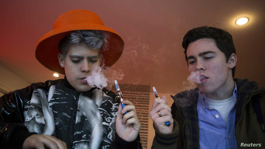 Customers puff on e-cigarettes at the Henley Vaporium in New York City December 18, 2013.