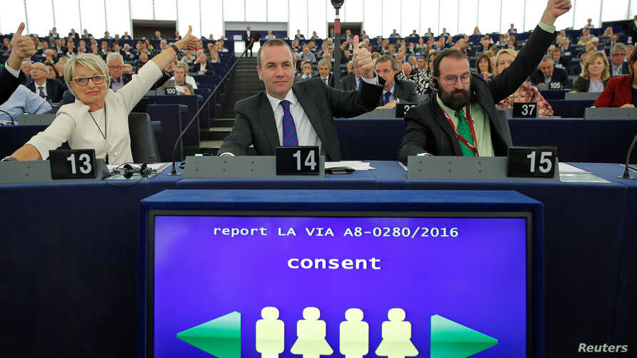 Members of the European Parliament vote in favor of the Paris climate change agreement during a voting session at the European Parliament in Strasbourg, Oct. 4, 2016.