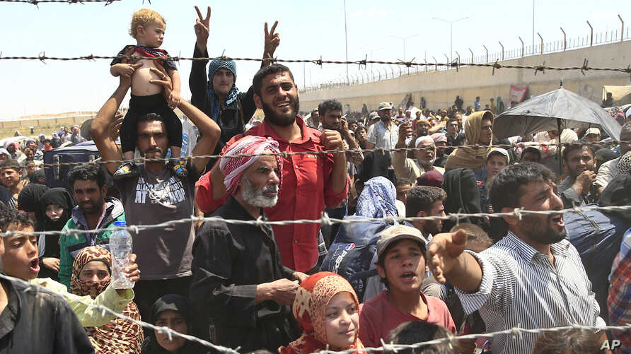Syrian refugees, flee intense fighting in northern Syria between Kurdish fighters and Islamic State militants, are seen massed at the Turkish border in Akcakale, southeastern Turkey, June 15, 2015.