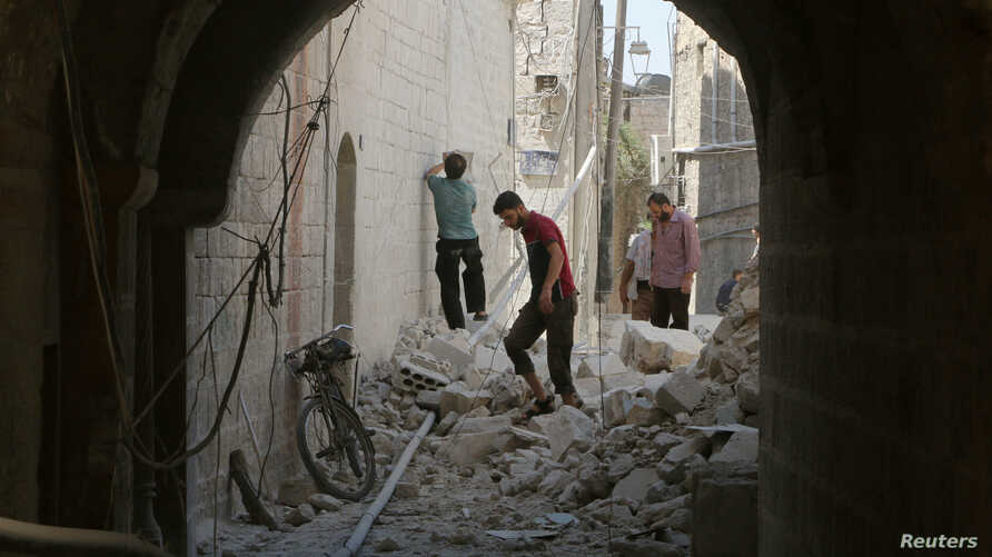 Residents inspect their damaged homes after an airstrike on the rebel-held Old Aleppo, Syria, Aug. 15, 2016.