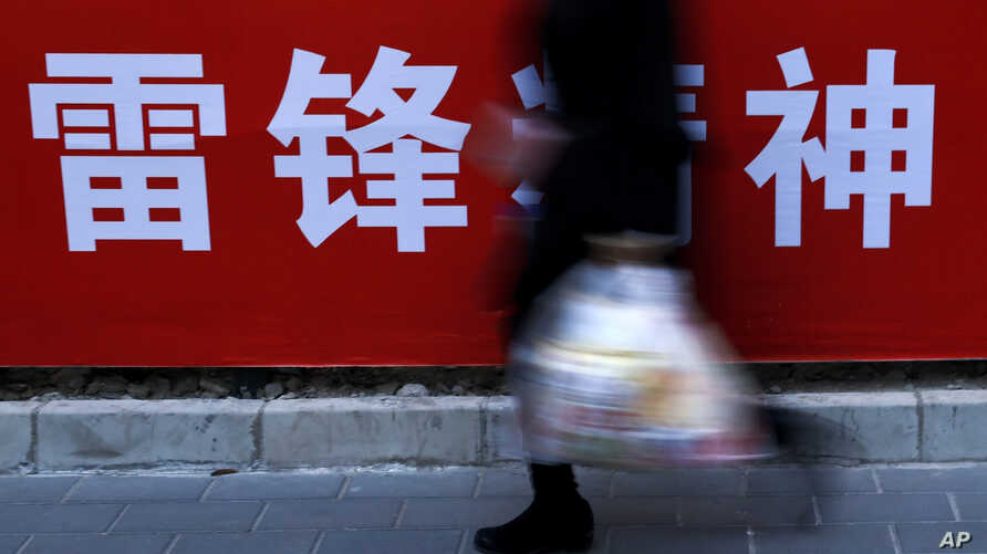 "A woman carries her groceries past a Chinese propaganda board depicting ""Lei Feng Spirit"" on a pavement in Beijing,  March 5, 2019."