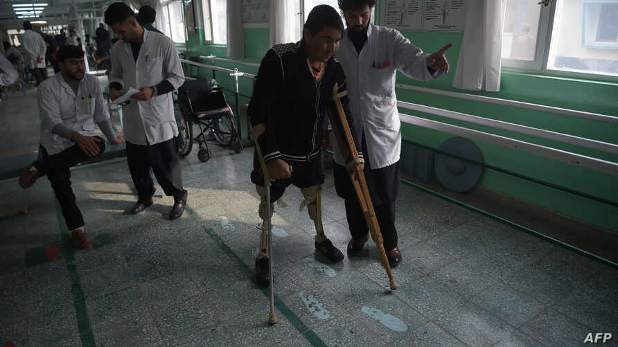 An Afghan doctor (R) assisting a survivor of a landmine blast at a hospital run by the International Committee of the Red Cross (ICRC) for war victims and the disabled in Kabul, Feb. 13, 2018.