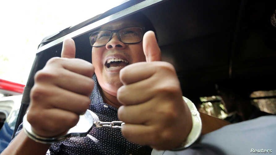 Detained Reuters journalist Wa Lone gestures to the media as he is escorted by police after a court hearing in Yangon, Myanmar, Apr. 11, 2018.