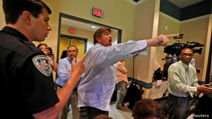 A man is escorted out of a town hall meeting with Republican U.S. Senator Bill Cassidy by law enforcement, in Metairie, Louisiana, Feb. 22, 2017.