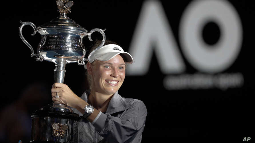 Denmark's Caroline Wozniacki holds her trophy aloft after defeating Romania's Simona Halep in the women's singles final at the Australian Open tennis championships in Melbourne, Australia, Jan. 27, 2018.