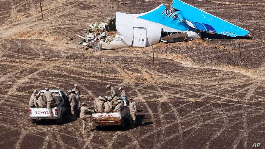 In this photo made available Monday, Nov. 2, 2015, and provided by Russian Emergency Situations Ministry, Egyptian Military on cars approach a plane's tail at the wreckage of a passenger jet bound for St. Petersburg in Russia that crashed in Hassana,