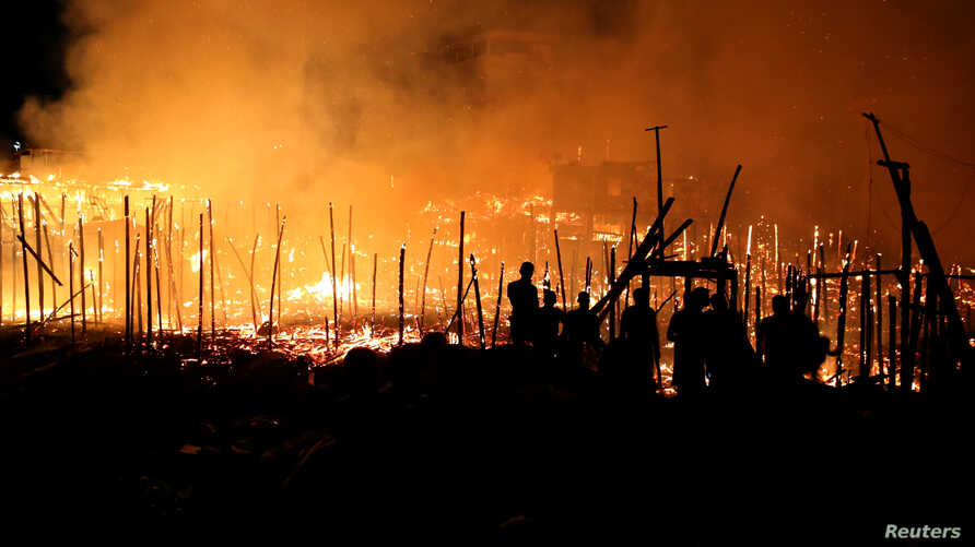 Houses on fire are seen at Educando neighbourhood, a branch of the Rio Negro, a tributary to the Amazon river, in the city of Manaus, Brazil Dec. 17, 2018.