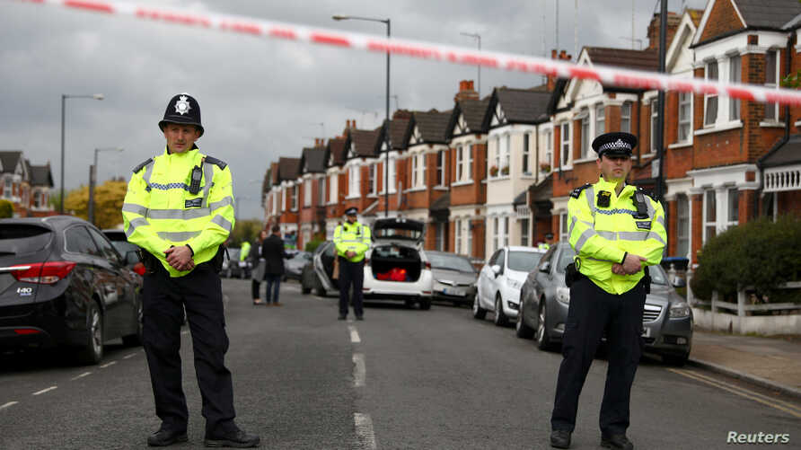 FILE - Police stand next to terraced housing in Harlesden Road, north London, April 28, 2017. British counterterrorism police said they had thwarted an active plot in an armed raid, the second major security operation in the British capital in the sp