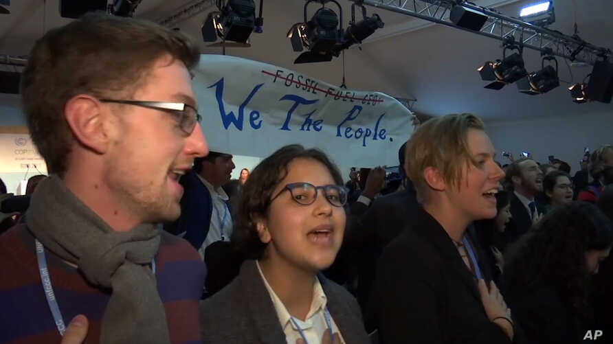 In this image made from video, protesters sing during climate talks at the World Climate Conference in Bonn, Germany, Nov. 13, 2017.
