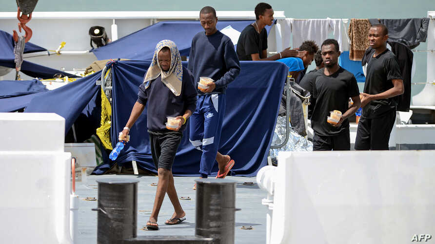 Migrants gather on the deck of the Italian Coast Guard vessel 'Diciotti' in the Sicilian port of Catania, on Aug. 23, 2018 as they wait to disembark following a rescue operation at sea.