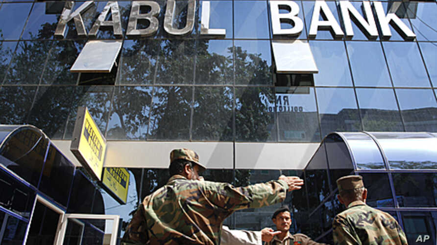 Afghan soldiers chat in front of the main office of Kabul Bank in Kabul, Afghanistan, Sept. 1, 2010.
