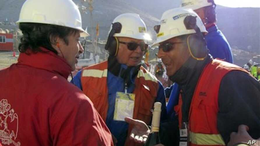 Chile's Minister of Mining Laurence Golborne, left, holds up a bottle of champagne as he speaks to unidentified members of the rescue team after the T-130 drill reached the 33 trapped miners at the San Jose mine near Copiapo, Chile Saturday Oct. 9, 2