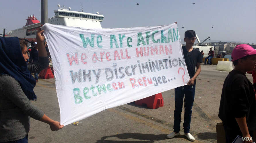 "Travelers from Afghanistan hold up a sign in protest of claims that they are ""economic migrants,"" rather than people who fled what some see as legitimate dangers before they have even applied for asylum in Athens, Greece, on April, 8, 2016. (H. Murdo"