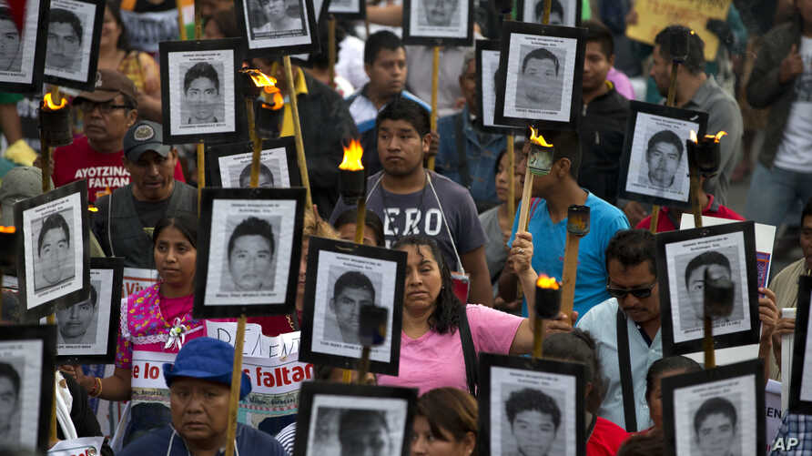 FILE - Family members and supporters of 43 missing teachers and college students from Guerrero state carry pictures of the missing students as they demand the case not be closed, in Mexico City, April 26, 2016.