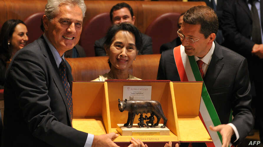 Nobel Peace laureate and Burmese opposition leader Aung San Suu Kyi (C) poses with the Mayor of Rome Ignazio Marino (R) and former minister and mayor of Rome Francesco Rutelli at the award ceremony at the Campidoglio in Rome October 27, 2013.