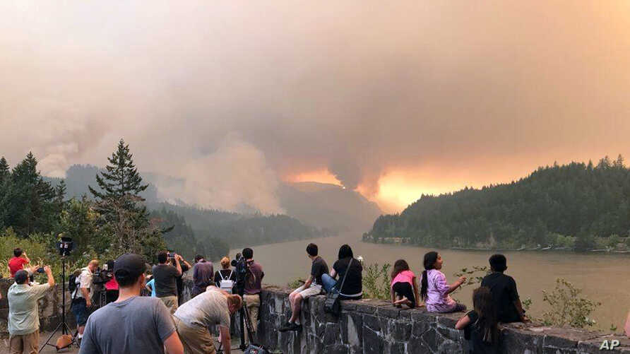 This photo, provided by Inciweb, shows people at a viewpoint overlooking the Columbia River watching the Eagle Creek wildfire burning in the Columbia River Gorge east of Portland, Ore., Sept. 4, 2017. A lengthy stretch of highway Interstate 84 remain