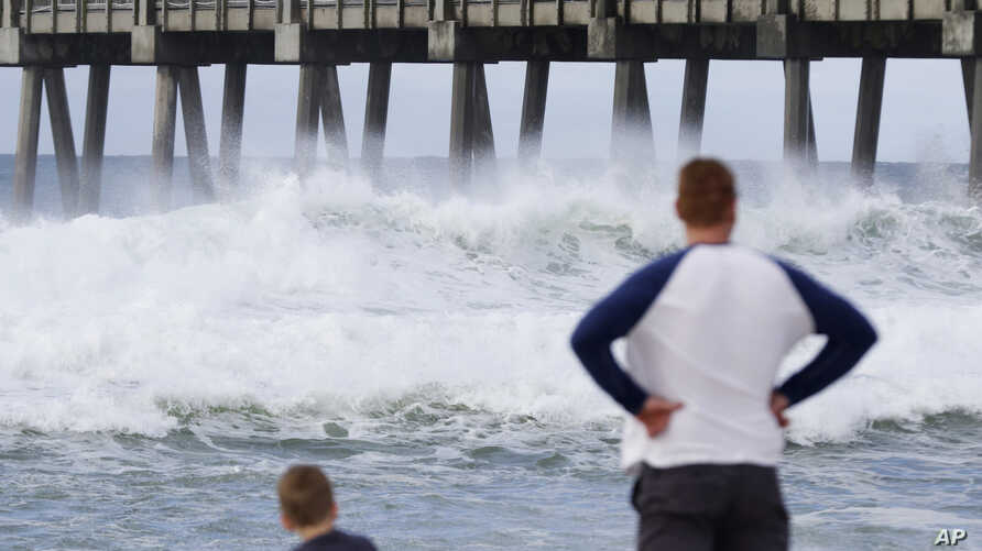 Harrison Westwood, 4, left, and his father Ben watch waves crash near the beach as a subtropical approaches on May 28, 2018, in Pensacola, Fla.