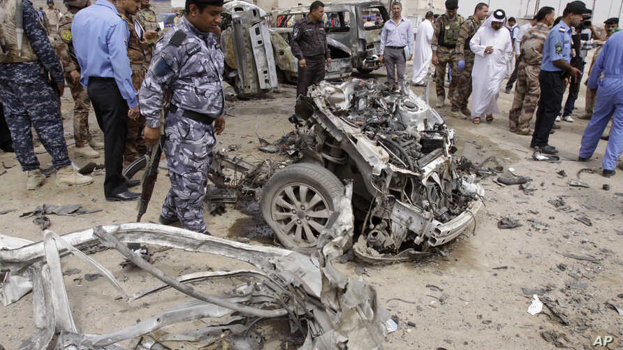 Iraqi security forces inspect the site of a car bomb attack in Basra, Iraq, March 17, 2013.