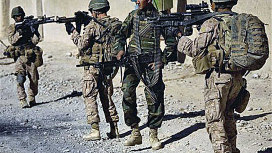 Lance Cpl. Juan Delacerda, of Kerrville, Texas, right, and Lance Cpl. Adam Rader, of Lodi, California, with India company, 3rd Battalion 5th Marines, First Marine Division, accompanied by an Afghan soldier patrol in Sangin, Afghanistan, Nov 11, 2010