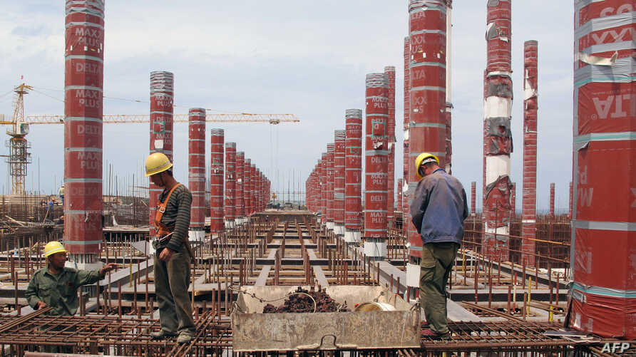 FILE - A picture taken on June 14, 2015 shows Chinese laborers working in Algiers at the construction site of the third largest mosque in the area and the largest in Africa.