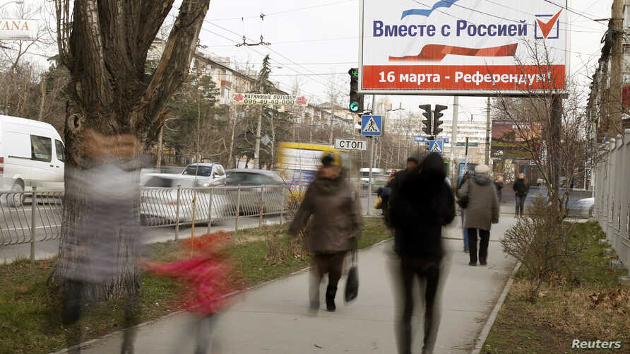 """People walk under a poster that reads, """"Together with Russia. March 16 - referendum"""", in the centre of Simferopol, March 12, 2014."""