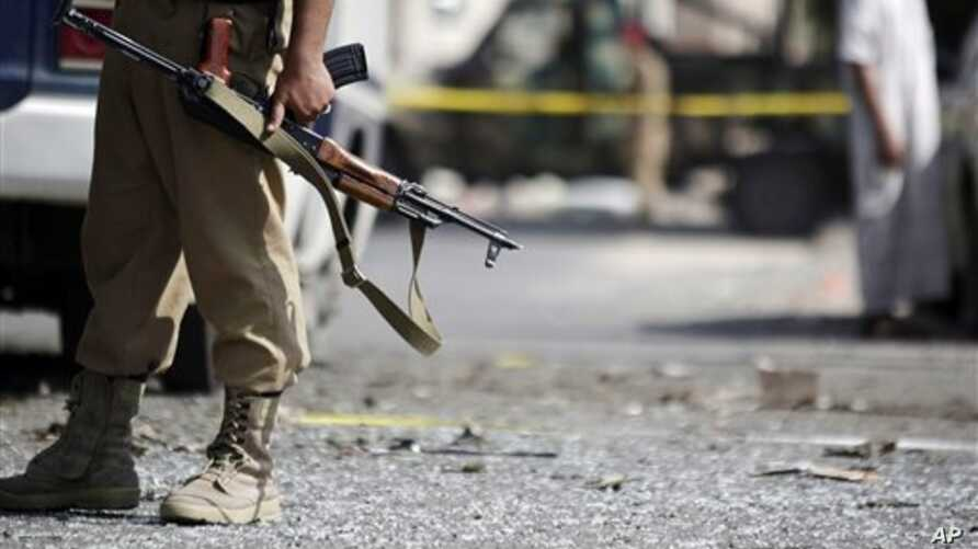 A Yemeni soldier stands guard at the site of a bomb attack on a bus in Sanaa, Yemen, Monday, Sept. 9, 2013. (AP Photo/Hani Mohammed)