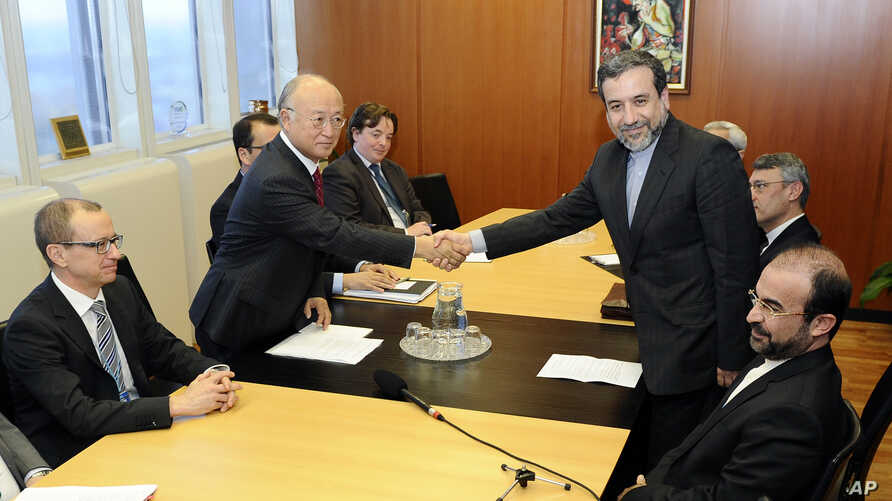 Iran's deputy Foreign Minister Abbas Araghchi, right, and Director General of the International Atomic Energy Agency, IAEA, Yukiya Amano shake hands prior to meeting in Vienna, Austria, Oct. 28, 2013.