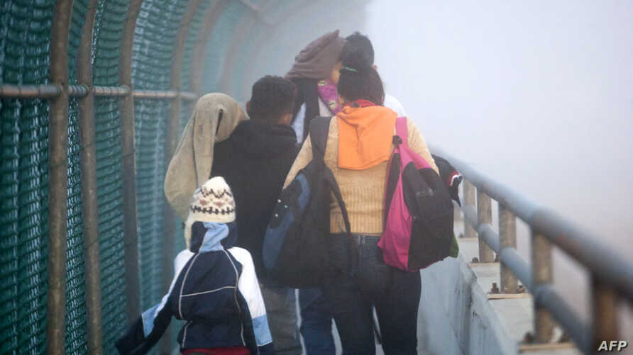 A Honduran family walks back to Piedras Negras, Coahuila state, Mexico at the international bridge, after being rejected by US authorities in their attempt to enter Eagle Pass, Texas, Feb. 6, 2019.