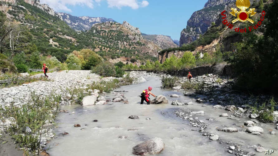 Firefighters search through the Raganello stream, Italy, looking for victims of a flash flood in the southern region of Calabria, Aug. 21, 2018