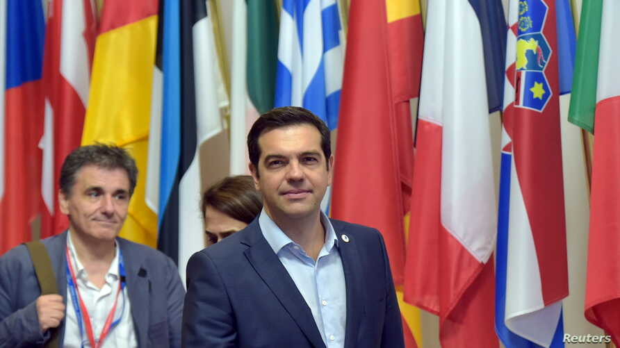 Greece's Prime Minister Alexis Tsipras (C) and Greek Finance Minister Euclid Tsakalotos (L) leave a eurozone leaders summit in Brussels, Belgium, July 13, 2015.