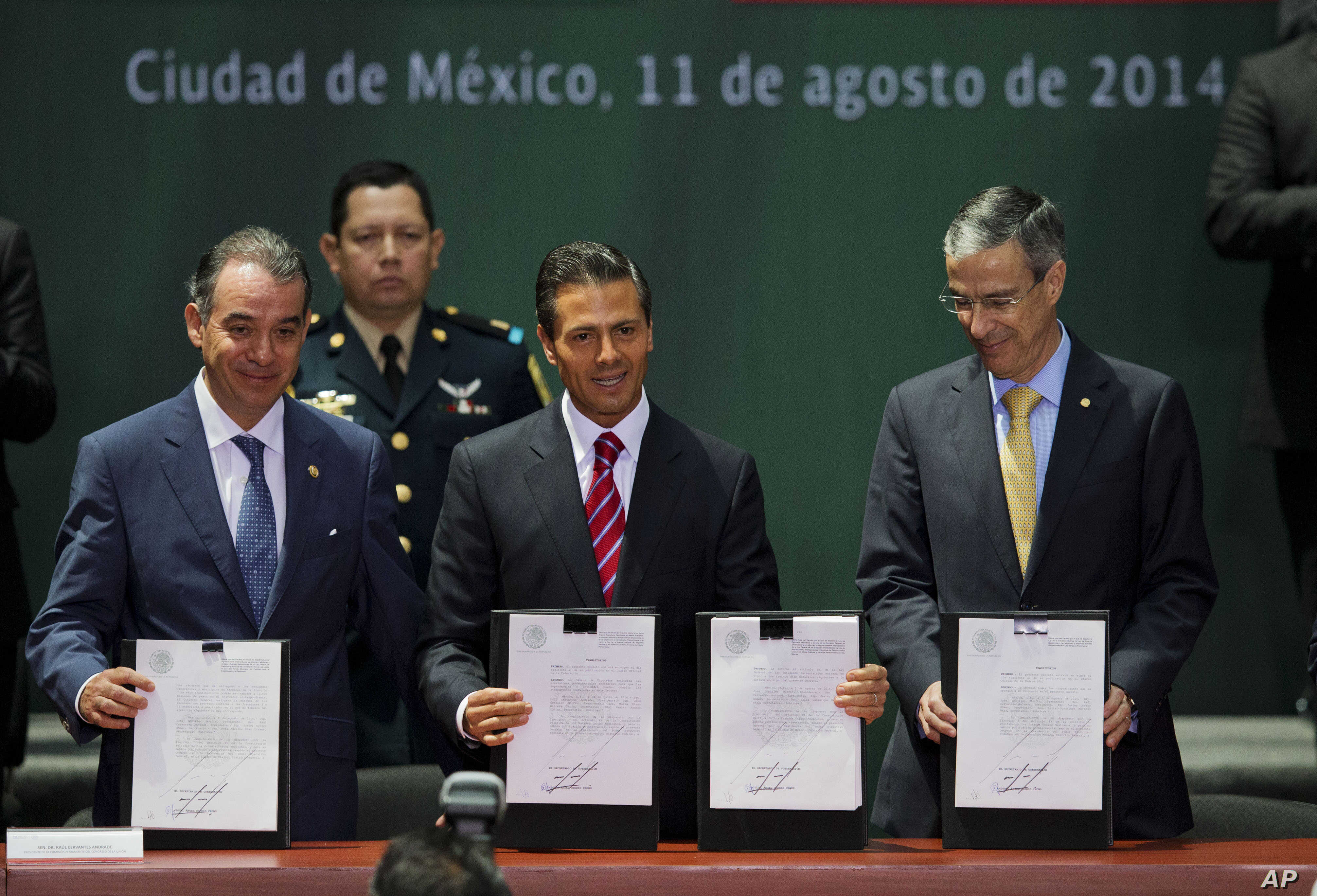 Mexican President Enrique Pena Nieto, center, Senate leader Raul Cervantes Andrade, left, and House Speaker Jose Gonzalez Morfin hold up signed documents at a ceremony to mark the signing of a historic energy reform bill, at the National Palace in Me