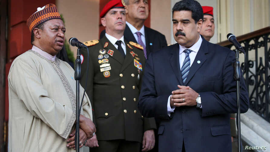 OPEC Secretary-General Mohammed Barkindo talks to reporters while standing with Venezuela's President Nicolas Maduro after their meeting at Miraflores Palace in Caracas, Venezuela, Nov. 16, 2016.