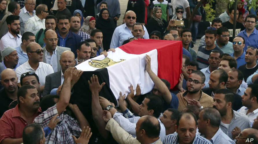 FILE - People carry the coffin, covered with the an Egyptian flag, of police Captain Ahmed Fayez at Al-Hosary mosque in Cairo, Oct. 21, 2017. Fayez was killed Oct. 20 in a gunbattle with militants in al-Wahat al-Bahriya area in Giza province, about 1