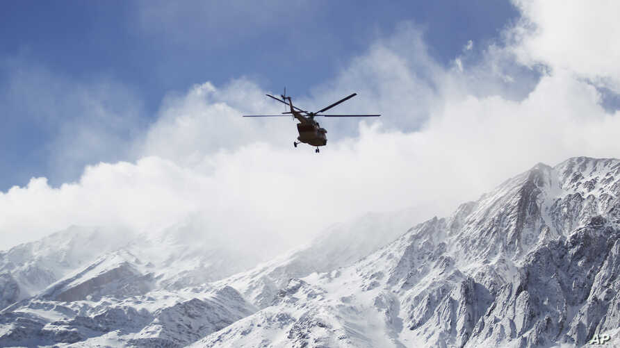 In this photo provided by Tasnim News Agency, a rescue helicopter flies over the Dena mountains while searching for wreckage of a plane in southern Iran, Feb. 19, 2018.