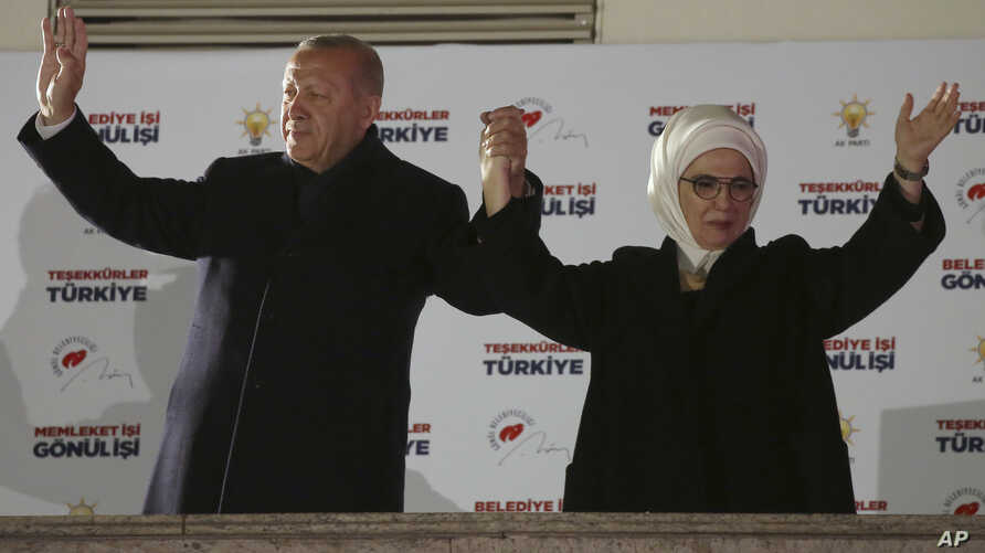 Turkey's President and ruling Justice and Development Party, or AKP, leader Recep Tayyip Erdogan, left, and his wife Emine, greet supporters after the results of the local elections were announced in Ankara, Turkey, early Monday, April 1, 2019.