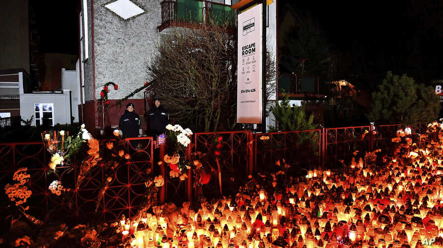 Lights, flowers and toys are left outside the escape room entertainment site where five teenage girls died in a fire last week, in Koszalin, northern Poland, Jan. 6, 2019.
