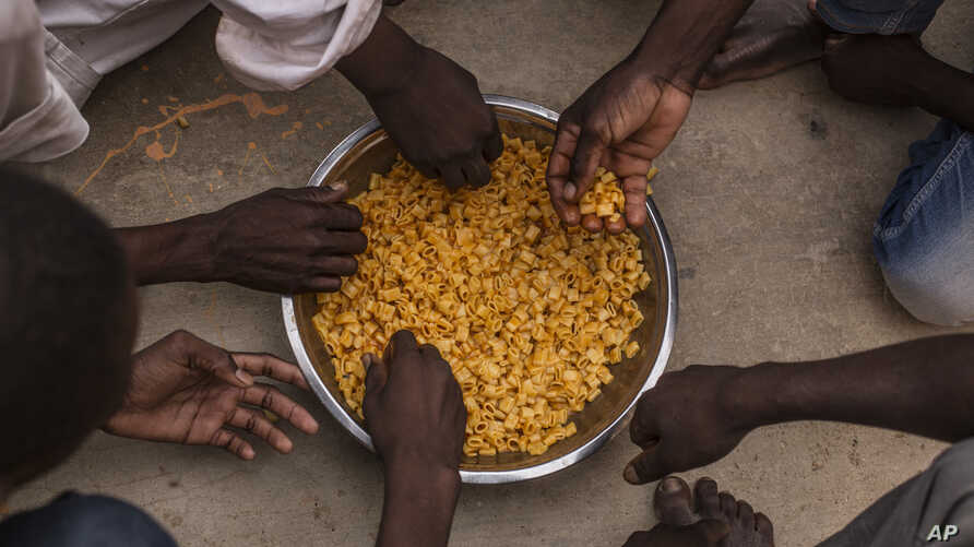 Migrants share a bowl of pasta during their lunch at the courtyard of a detention center for migrants, in the village of Karareem, around 50 km from Misrata, Libya, September 25, 2016. Libya is an important transit and destination country for migrant