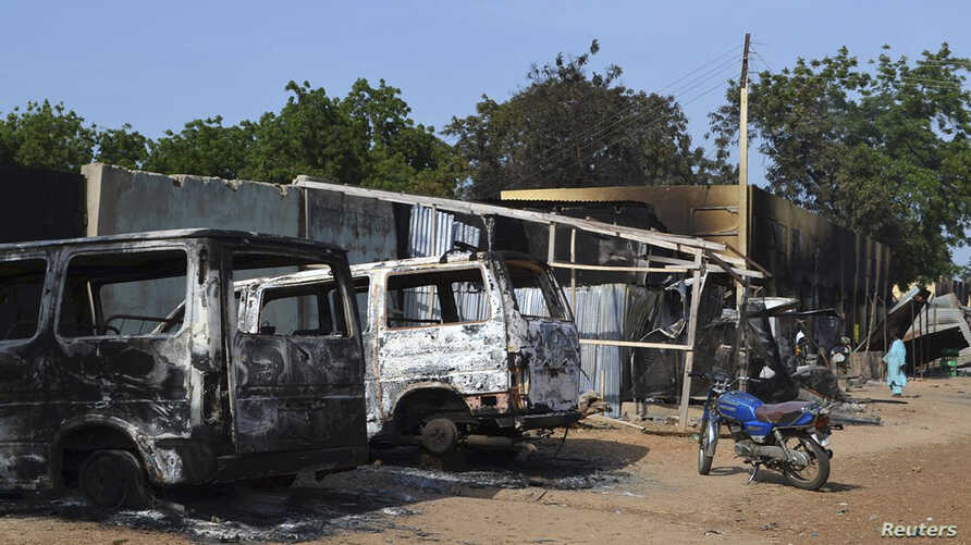 FILE - Burnt vehicles and houses are pictured on a street, after Boko Haram militants raided the town of Benisheik, west of Borno State capital Maiduguri.