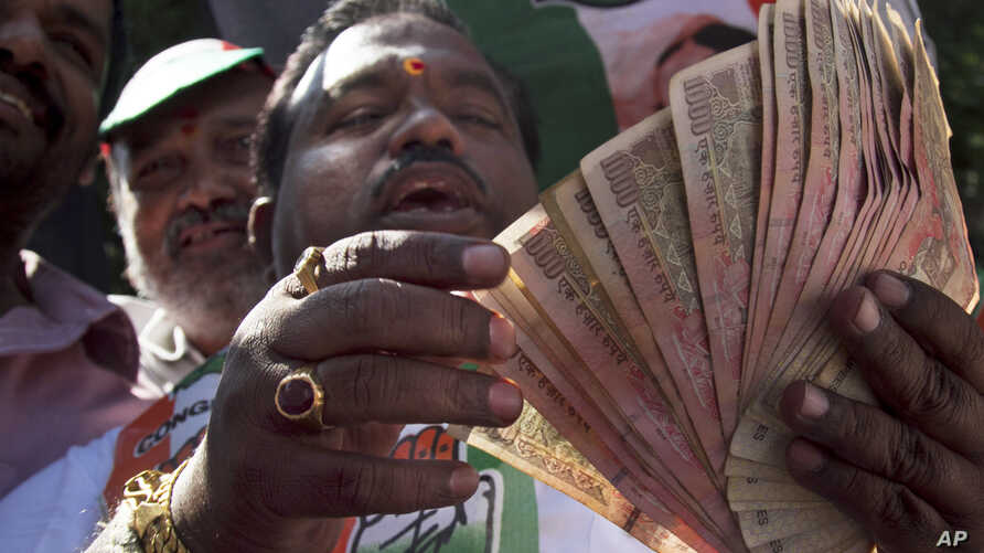 An activist of Congress party holds banned 500 and 1000 rupee notes during a protest against the government's decision to withdraw high denomination notes from circulation, in front of Reserve Bank of India. in Hyderabad, Nov. 28, 2016.