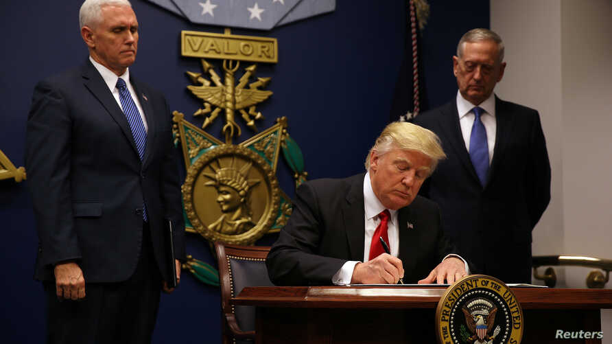 President Donald Trump signs an executive order he said would impose tighter vetting to prevent foreign terrorists from entering the United States at the Pentagon in Washington, Jan. 27, 2017.