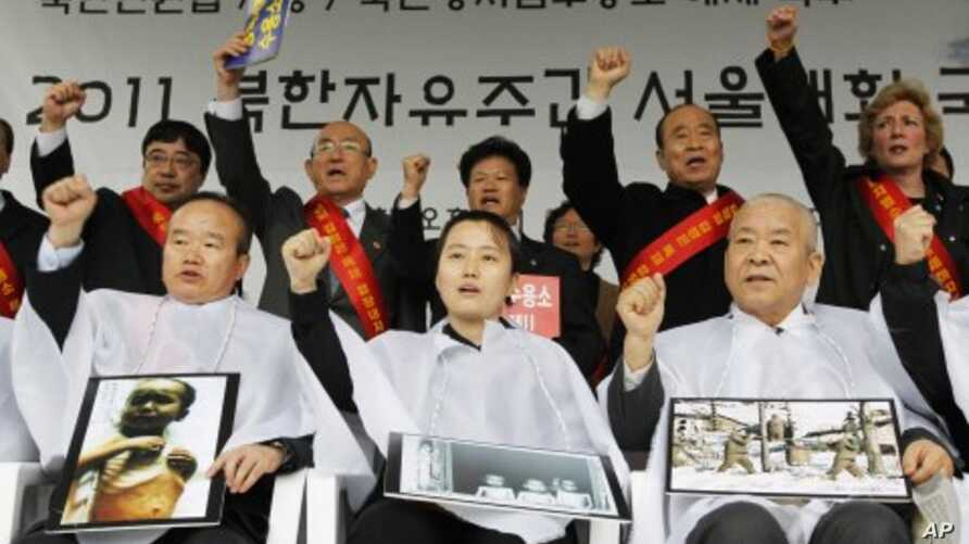 Participants holding pictures of a Northern prison camp and N. Korean children in hunger shout slogans after they got their heads shaved during an anti-North Korea rally demanding a legislation of N. Korean human rights laws at a plaza in front of th
