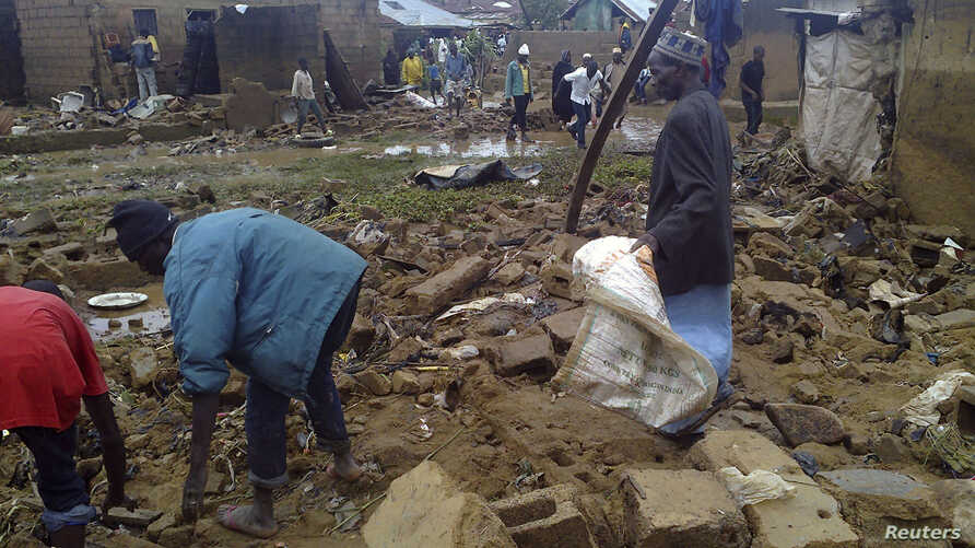 Residents sort through the ruins of a building after a flood devastates Nigeria's central city of Jos, July 24, 2012.