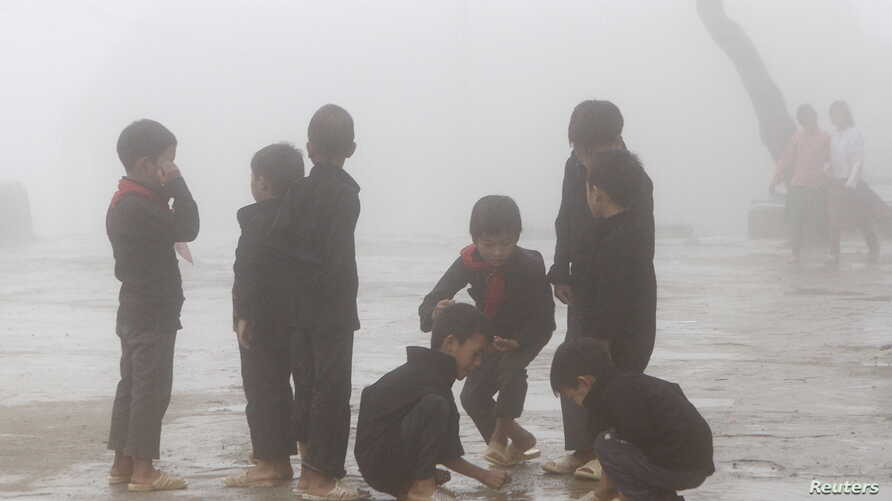 FILE - Hmong children play during a class break on a foggy day at Van Chai school in Dong Van district of Vietnam's northern province of Ha Giang, located on the border with China on Sept. 21, 2015.