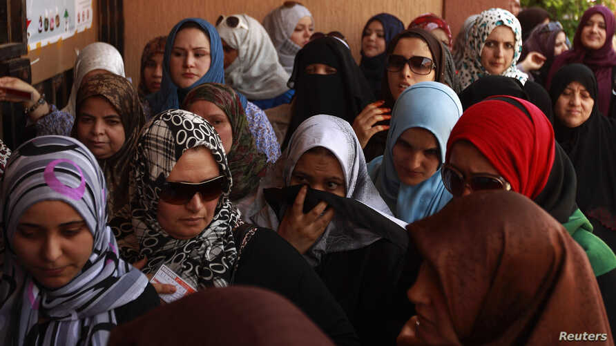 FILE - Women queue to cast their ballot at a polling station during the National Assembly election in Tripoli, July 7, 2012.