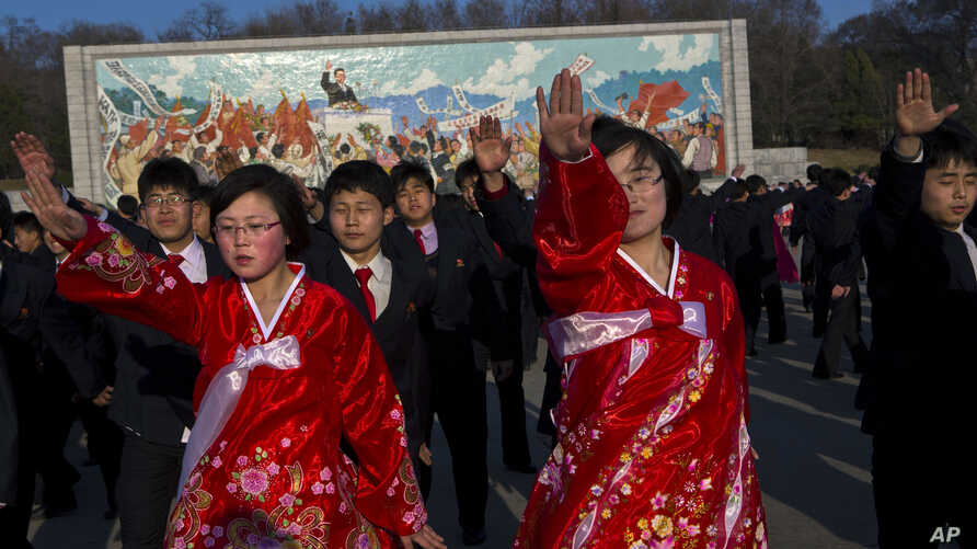 North Koreans dance together beneath a mosaic painting of the late leader Kim Il Sung during a mass folk dancing gathering in Pyongyang, April 11, 2013.