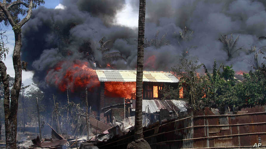 Smokes and flames billow from burning buildings in Sittwe, capital of Rakhine state in western Burma, where sectarian violence is ongoing, June 12, 2012.