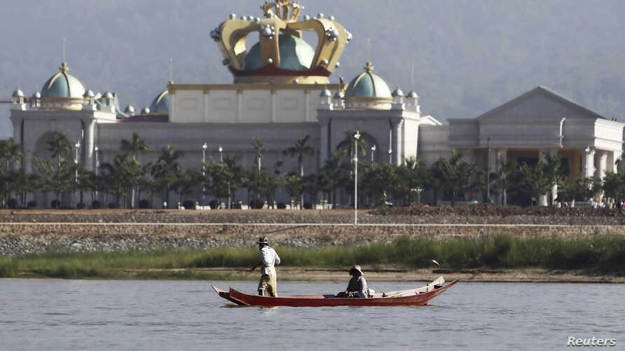 People maneuvre a small boat along the Mekong river in front of the Kings Roman casino opposite Sop Ruak in the Golden Triangle region where the borders of Thailand, Laos and Myanmar meet, Jan. 15, 2012.
