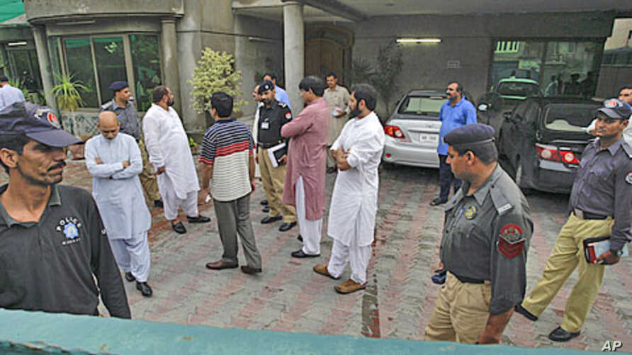 Pakistani security officials gather at the compound of the house of a abducted American citizen in Lahore, Pakistan, Aug. 13, 2011