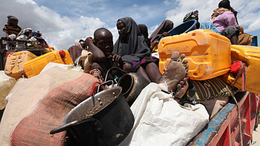 Internally displaced families wait to board trucks as they travel back to their home regions from Ala-yasir camp closed by the al Shabaab militias, in Lower Shabelle, 50 km (31 miles) south of Somalia's capital Mogadishu, October 15, 2011.
