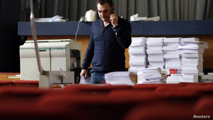 Roman Lyagin, leader of the separatist republic's election commission, talks on a mobile phone at the commission headquarters in Donetsk, eastern Ukraine, May 8, 2014.